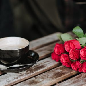 faceless couple with coffee and rose bouquet in cafeteria